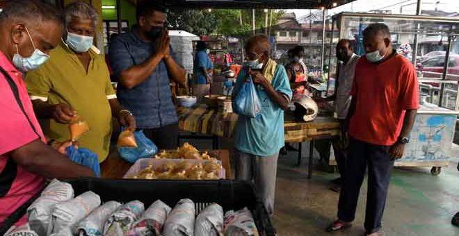 SANTUNI BARISAN HADAPAN: M.Moganasundram memberi makanan percuma berbentuk 100 bungkus nasi berlauk setiap hari sehingga tempoh Perintah Kawalan Pergerakan (PKP) tamat. — Gambar Bernama