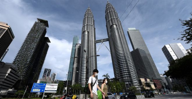 Pasangan pejalan kaki melintasi persimpangan lampu isyarat Jalan Ampang, Kuala Lumpuryang kelihatan agak lengang semasa PKP, April 2020. - Gambar fail Bernama