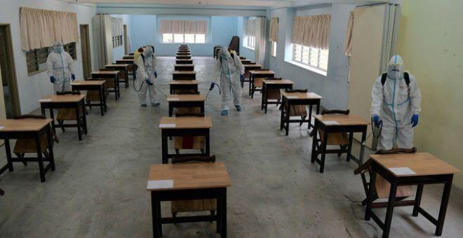 Anggota Bomba dan Penyelamat menjalankan kerja-kerja disanitasi dan disinfeksi dalam bilik darjah yang digunakan bagi peperiksaan Sijil Pelajaran Malaysia (SPM) 2020 bermula esok di Sekolah Menengah Kebangsaan Majidee Baru 2, hari ini. - Gambar Bernama