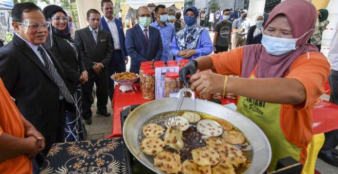 Ronald bersama timbalannya Datuk Seri Ahmad Hamzah (kiri) dan Ketua Setiausaha kementerian itu Datuk Haslina Abdul Hamid (dua, kiri) singgah di gerai menjual rempeyek kacang selepas merasmikan Program My Best Buy Aidilfitri di kementeriannya hari ini. - Gambar Bernama