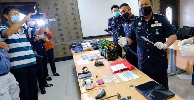 TUMPAS: ACP A. Asmadi (kanan) menunjukkan barangan yang dirampas pada sidang media mengenai kes pecah kedai dobi dan kedai runcit di Ibu Pejabat Polis Daerah Ipoh, dekat Ipoh semalam. — Gambar Bernama