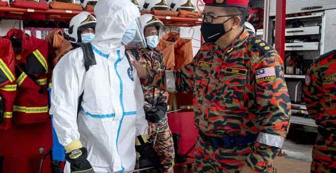 SANTUNI ANGGOTA: Jainal @ Zainal Madasin (kanan) meninjau anggota Bomba dan Penyelamat membuat persediaan bagi menghadapi musim perayaan sempena Majlis Penyampaian Buah Kurma Sumbangan Perdana Menteri Ibu Pejabat JBPM Negeri Kelantan, Kota Bharu semalam. — Gambar Bernama