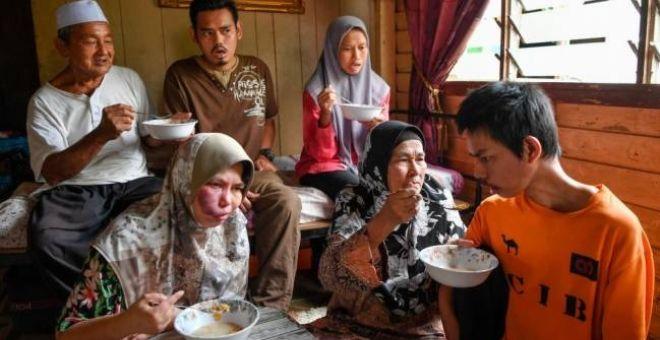 Azizah (dua, kanan) dibantu suami Kamaludin Embong, 70, menyuapkan sarapan pagi kepada anak-anaknya Orang Kurang Upaya (OKU) ketika ditemui di Kampung Keliyu. - Gambar Bernama.
