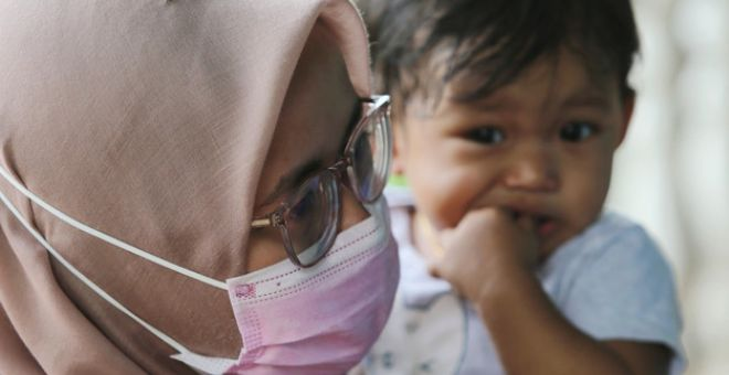 Nor Fitrah memangku anaknya, Anurasyfa Alisha 1, ketika ditemu bual wartawan di kediamanya di Felda Bukit Damar Lanchang pada Sabtu. - Gambar Bernama