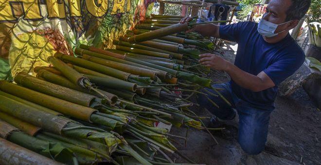 PERIKSA: Jeffrey memeriksa sebahagian batang buluh yang sudah dimasukkan daun lerek ketika ditemui Bernama di Kampung Mahligai di Bachok semalam. — Gambar Bernama