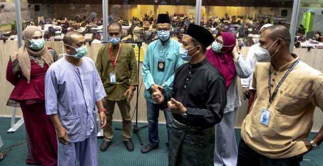 PRIHATIN: Dr Mohd Azman (dua kanan) bertanya sesuatu kepada seorang pesakit sempena tinjauan di Pusat Kuarantin dan Rawatan COVID-19 Berisiko Rendah (PKRC) Negeri Kelantan semalam. — Gambar Bernama