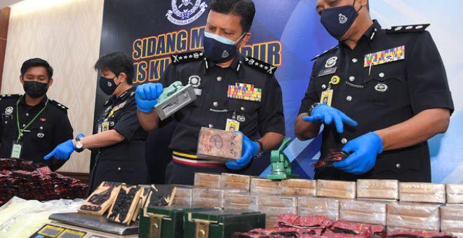 Azmi (dua, kanan) bersama pegawai yang bertugas menunjukkan rampasan dadah jenis heroin base dianggarkan bernilai RM9.3 juta ketika sidang media di Ibu Pejabat Polis Kontinjen Kuala Lumpur hari ini. - Gambar Bernama