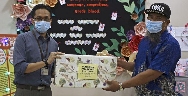 TANDA PENGHARGAAN: Dr Firdaus Che Ros (kiri) menyampaikan cenderahati kepada penderma darah tertinggi Nor Aziman iaitu sebanyak 100 kali menderma darah ketika ditemui Bernama sempena Hari Derma Darah Sedunia di Pusat Derma Darah di Seremban, semalam. — Gambar Bernama