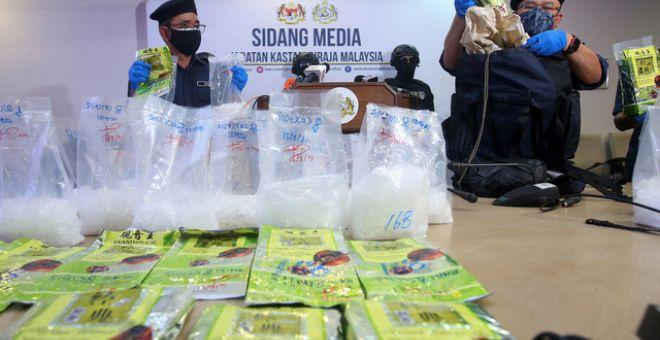 Abdul Latiff menunjukkan bungkusan teh yang menyimpan ketulan mampat dadah dipercayai jenis Methaphetamine di dalam sebuah beg yang dirampas pada sidang media di Ibu Pejabat JKDM Cawangan Narkotik Kampung Jijan, hari ini. -Gambar Bernama