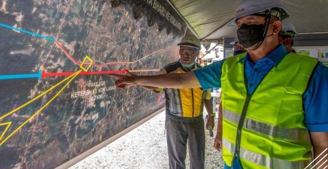 Fadillah (kanan) melihat peta projek Lebuh Raya Kota Bharu-Kuala Krai di tapak projek berkenaan dekat Kok Lanas, Ketereh hari ini. -Gambar Bernama
