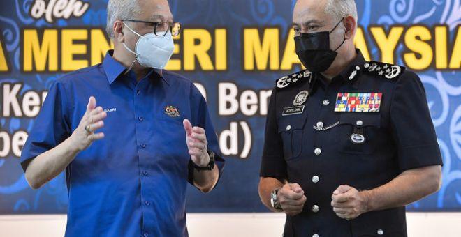 Ismail Sabri (kiri) memperkatakan sesuatu kepada Acryl Sani pada Upacara Pemakaian Pangkat Ketua Polis dan Timbalan Ketua Polis Daerah Bera hari ini. - Gambar Bernama