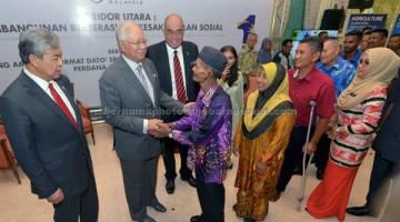 TERIMA BANTAUN: Najib bersalaman dengan Mahmod Mat Saman, 70, serta para penerima manfaat dalam program-program berpaksikan rakyat oleh Pihak Berkuasa Pelaksanaan Koridor Utara (NCIA) sambil disaksikan Timbalan Perdana Menteri, Datuk Seri Dr Ahmad Zahid Hamidi dan Ketua Eksekutif NCIA, Datuk Redza Rafiq (tiga kiri) selepas mempengerusikan mesyuarat Pihak Berkuasa Pelaksanaan Koridor Utara (NCIA) di Bangunan Perdana Putra, Putrajaya semalam. — Gambar Bernama