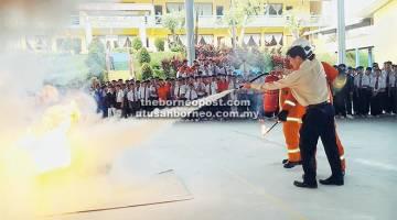 PADAM: Demonstrasi memadam api dengan menggunakan alat pemadam api jenis serbuk melibatkan penyertaan warga sekolah sambil dipantau oleh anggota bomba.