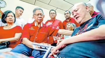 PRIHATIN: Mustapha (dua, kiri) mendengar keluhan Seiw Chee Wei, 59, (duduk) ketika melawat pesakit saraf itu sempena Tahun Baharu Cina di kediamannya Jalan Telipoi semalam. — Gambar Bernama