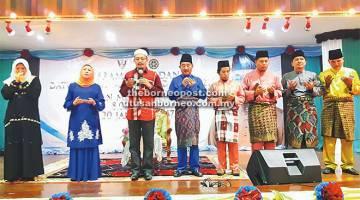 MEMOHON KEBERKATAN: Ustaz Kazim (tiga kiri) mengetuai bacaan doa bersama Nancy (dua kiri), Awla (lima kanan) dan hadirin yang lain.