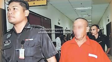 HUKUMAN DITAMBAH: Tertuduh yang memakai pakaian seragam penjara berwarna merah diiringi oleh pegawai Jabatan Penjara.
