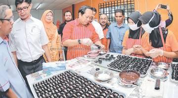 TUNJUK BAKAT: Ahmad Maslan (tengah) meletakkan biskut coklat ke dalam bekas sewaktu meninjau pembuatan biskut selepas merasmikan kilang biskut RMT Timur Qaseh Sdn Bhd di Ajil, semalam. — Gambar Bernama