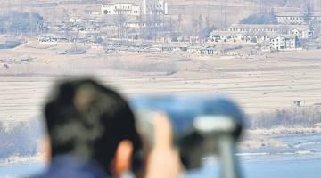 PROVOKASI: Seorang lelaki meneropong kampung propaganda Kaepoong dari pelantar tinjau dekat zon tanpa tentera yang memisahkan kedua-dua negara Korea di Paju, semalam. — Gambar Reuters