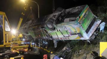 MALANG: Kren mengangkat bangkai bas yang remuk di tempat kejadian berhampiran Taipei, semalam. — Gambar AFP