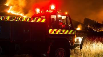 TERBAKAR: Anggota bomba dikerah untuk menangani kebakaran hutan di Christchurch, New Zealand semalam. — Gambar AFP