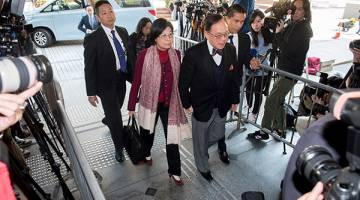 RASUAH?: Bekas pemimpin Hong Kong Donald Tsang bersama isterinya tiba di Mahkamah Tinggi di Hong Kong semalam. — Gambar AFP