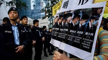 PROTES: Anggota polis (kiri) berkawal ketika penyokong prodemokrasi (kanan) melaungkan slogan dan memegang plakad selepas ketibaan tujuh anggota polis (gambar tertera pada plakad kanan), yang didapati bersalah pada 14 Februari kerana menyerang aktivis                 Ken Tsang ketika tunjuk perasaan prodemokrasi pada 2014, di luar Mahkamah Daerah di Hong Kong semalam. — Gambar AFP