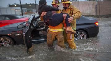 BERJAYA DISELAMATKAN: Anggota bomba mengangkat keluar seorang wanita dari kereta selepas terperangkap di jalan yang dilanda banjir selepas satu ribut petir bergerak melanda  Selatan California kelmarin di Sun Valley, California. — Gambar AFP