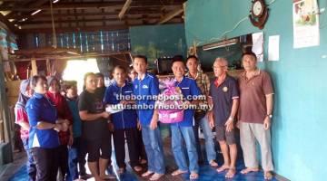 TANGGUNGJAWAB SOSIAL: Han (enam kanan) dan Zaidi (lima kanan) menyerahkan sumbangan kepada ahli keluarga Yut (empat kiri) sambil diperhati oleh ahli-ahli KRT Jalan Bajai/Kampung Hilir dan KRT Kampung Sungai Ud/Kampung Tengah.