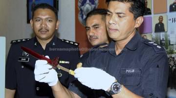 TUMPAS: M Chandra menunjukkan pisau Badik yang ditemui di dalam kenderaan yang digunakan oleh ahli kumpulan Geng Hitam untuk melakukan samun di beberapa kawasan sekitar dekat Kinabalu, semalam. — Gambar Bernama