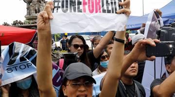 SOKONG SENATOR: Penyokong Senator Filipina Leila De Lima mempamer plakad ketika menyertai perhimpunan di luar sebuah mahkamah di Muntinlupa, Metro Manila, semalam. — Gambar Reuters