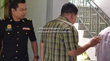 TUNTUTAN PALSU: Wan Akil (kanan) diiringi oleh seorang pegawai SPRM keluar dari mahkamah setelah dijatuhkan hukuman atas tuduhan mengemukakan tuntutan elaun perjalanan palsu.