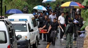 MAUT: Polis mengangkat mayat salah seorang mangsa yang ditembak mati di daerah Ruso, di wilayah selatan Thailand, Narathiwat semalam. — Gambar Reuters