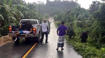 INSIDEN BERDARAH: Anggota keselamatan Thailand membantu mengalihkan mangsa kejadian tembak di Kampung Thammacharen, Mukim Khok Setor di Narathiwat kelmarin. — Gambar Bernama