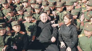 MASA BERGEMBIRA: Kim Jong-un melawat Sekolah Revolusi Mangyongdae bersama isterinya dan menanam pokok bersama para pelajarnya sempena Hari Menanam Pokok pada Khamis lalu, dalam gambar serahan KCNA di Pyongyang, kelmarin. — Gambar Reuters