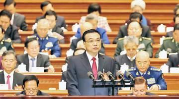 TEGAS: Li menyampaikan laporan kerja kerajaan semasa sesi pembukaan Kongres Rakyat Nasional (NPC) di Dewan Besar Rakyat di Beijing, semalam. — Gambar Reuters