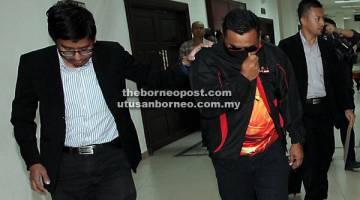 DIDAKWA: Tertuduh (kanan) dibawa keluar selepas sebutan pertuduhan di Mahkamah           Khas Rasuah di Kuching semalam.