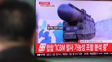 PROVOKASI: Laporan berita di televisyen yang menunjukkan rakaman arkib pelancaran misil Korea Utara disiarkan pada skrin awam di Seoul, semalam. — Gambar AFP