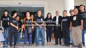 TUNTUT KEADILAN: Hasyikin (enam kanan) dan ahli keluarga bergambar bersama Majen (memakai kot) selepas sesi perbicaraan tengah hari semalam.