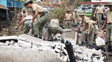MEMBANTU: Seramai 55 angota tentera dari 11RAMD menyertai Program Jiwa Murni ATM 2017 di kawasan kediaman Piot di Kampung Pinang Jawa, Kuching.