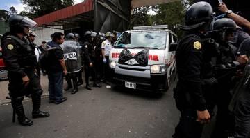 TRAGEDI: Sebuah ambulans beredar dari Virgen de Asuncion Safe Home di San Jose Pinula, pinggir Guatemala City kelmarin. Gambar kiri menunjukkan salah seorang mangsa terselamat, Daniel, 16, dipapah keluar dari tempat kejadian. — Gambar Reuters