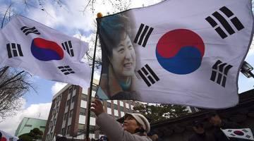 TETAP SOKONG: Aktivis prokerajaan mengibarkan bendera negara menunjukkan potret Park ketika menyertai perhimpunan berhampiran Mahkamah Perlembagaan untuk membantah pendakwaan presiden oleh Parlimen dalam skandal rasuah berskala besar di Seoul, kelmarin. — Gambar AFP