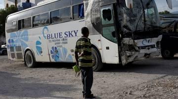 TRAGIK: Seorang lelaki melihat bas yang terlibat dalam kemalangan tersebut di tempat parkir balai polis Gonaives, kelmarin. — Gambar Reuters