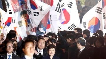 TERSENYUM: Park bertegur sapa dengan para penyokongnya sejurus tiba di kediaman peribadinya di Seoul, semalam. — Gambar Reuters