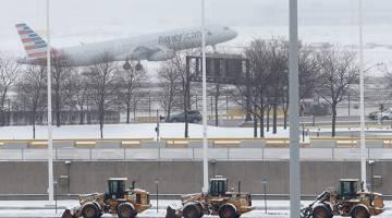 SIAP SEDIA: Jentera berat membersihkan salji dari lebuh raya ketika sebuah pesawat American Airlines berlepas dalam ribut salji di Lapangan Terbang Antarabangsa O'Hare di Chicago, Illinois kelmarin. — Gambar Reuters