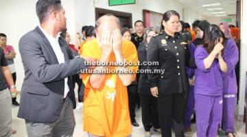REMAN: Sebahagian daripada 11 pegawai imigresen Sarawak kelihatan dibawa keluar dari Mahkamah Majistret, Kuching semalam.