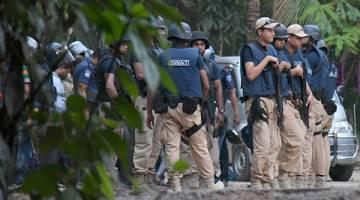SEDIA BERTINDAK: Anggota pasukan keselamatan Bangladesh dilihat bersedia untuk menyerbu sebuah rumah di mana kumpulan pelampau Islam disyaki bersembunyi di Chittagong kelmarin. — Gambar AFP