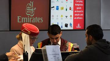 DIPERKETAT: Seorang penumpang membeli tiket di kaunter Emirates Airline berlatarbelakangkan skrin amaran barangan berbahaya di Lapangan Terbang Antarabangsa Los Angeles di Los Angeles, California kelmarin. — Gambar AFP