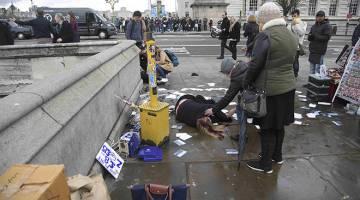 PARAH: Orang ramai membantu wanita yang cedera selepas serangan di Jambatan Westminster di London kelmarin. — Gambar Reuters