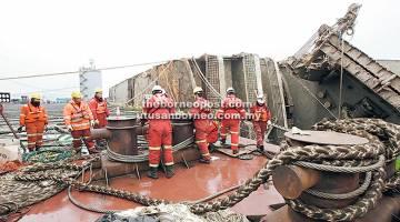 TUGAS BERAT: Gambar menunjukkan bangkai feri Sewol di antara dua kapal angkat berat gergasi semasa usaha untuk membawa balik kapal tersebut ke pelabuhan di laut di luar pulau Jindo, Korea Selatan kelmarin. — Gambar AFP