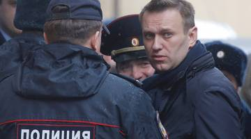 PENGKRITIK LANTANG: Navalny (kanan) dieskot para pegawai polis sebaik tiba di mahkamah Tverskoi di Moscow, semalam untuk pendengaran kesnya. — Gambar Reuters